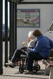 Enjoyable Moment. Elderly lady in a wheelchair eating an ice cream and sitting next to a female carer in a bus shelter royalty free stock image