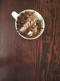 An enjoyed mocha with foam art and chocolate swirls, on a wooden background Stock Photos