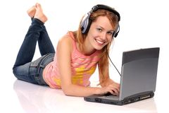 Enjoying. Young beautiful woman with laptop and headphones, isolated on white Stock Image