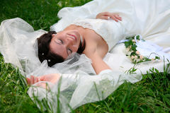 Enjoying. Photo of enjoying woman with closed eyes lying on the grass after marriage Stock Photos
