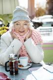 Cheerful mature lady relaxing in cafe outside Stock Images