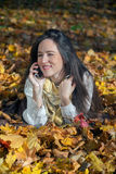 Enjoying in autumn and talking on mobile phone. Stock Photos