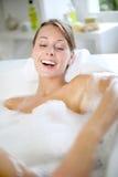 Enjoying bath time. Cheerful young woman enjoying bath time royalty free stock photos