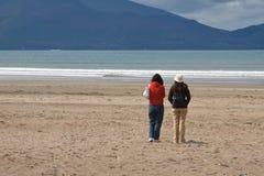 Enjoying the beach. Two young women enjoying the beach at Inch Strand in Ireland stock photo