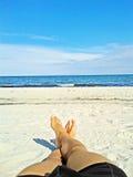 Enjoying the beach - male feet, sand, ocean Stock Image