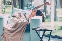 Enjoying beautiful morning. Beautiful young woman stretching out hands and smiling while lying in a big comfortable chair at home Royalty Free Stock Photography