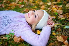 Enjoying beauty of nature. A pretty young girl is lying on the ground with golden leaves. Autumn fashion, beauty royalty free stock image