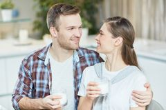 Enjoying breakfast. Yougn men and women with glasses of milk looking at one another and talking by breakfast Stock Photo