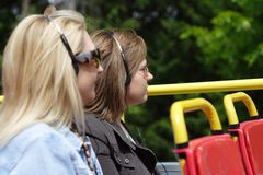 Enjoying a bus tour. Two women enjoying an open top bus tour of the city (Bath royalty free stock photography