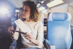 Enjoying business travel concept. Young beautiful brunette tourist girl travelling on the train sitting near the window. Using smartphone,holding ticket hands Stock Photo