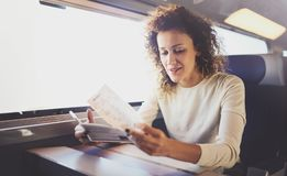 Enjoying business travel concept. Young beautiful brunette tourist girl travelling on the train sitting near the window. Using smartphone,holding ticket hands Royalty Free Stock Image
