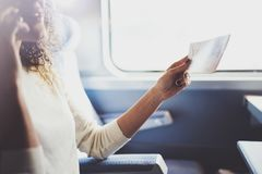 Enjoying business travel concept. Young beautiful brunette tourist girl travelling on the train sitting near the window. Using smartphone,holding ticket hands Stock Photography