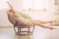 Enjoying carefree time at home. Cheerful young woman keeping eyes closed and stretching out hands while sitting in big comfortable chair at home Royalty Free Stock Image