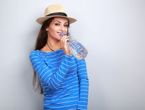 Enjoying casual woman in summer hat drinking pure water from bot. Tle on blue background Royalty Free Stock Photo