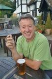 Enjoying a cigar and pint. Man enjoying a cigar and pint of beer outside an English pub Royalty Free Stock Photos