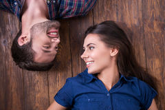 Enjoying closeness. Top view of beautiful young loving couple lying together on the hardwood floor and looking at each other Stock Photography