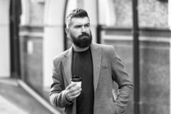 Enjoying coffee on the go. Businessman well groomed appearance enjoy coffee break out of business center. Relax and. Recharge. Man bearded hipster drinking stock photography