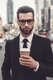 Enjoying coffee on the go. Confident young man in full suit holding coffee cup and looking at camera while standing outdoors with cityscape in the background Royalty Free Stock Photography