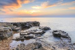 Enjoying the colorful sunset on a beach with rocks on the Adriatic Sea coast Istria Croatia. Colorful sunset on a beach with rocks on the Adriatic Sea coast royalty free stock photography