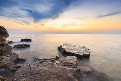 Enjoying the colorful sunset on a beach with rocks on the Adriatic Sea coast Istria Croatia stock photo