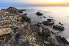 Enjoying the colorful sunset on a beach with rocks on the Adriatic Sea coast Istria Croatia stock image
