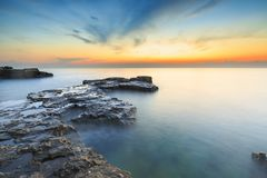 Enjoying the colorful sunset on a beach with rocks on the Adriatic Sea coast Istria Croatia. Colorful sunset on a beach with rocks on the Adriatic Sea coast stock images