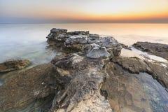 Enjoying the colorful sunset on a beach with rocks on the Adriatic Sea coast Istria Croatia. Colorful sunset on a beach with rocks on the Adriatic Sea coast stock photo