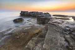Enjoying the colorful sunset on a beach with rocks on the Adriatic Sea coast Istria Croatia. Colorful sunset on a beach with rocks on the Adriatic Sea coast stock photos
