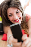 Enjoying content on her smartphone Royalty Free Stock Photos