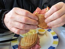Eating a Sandwich. Enjoying a corned beef sandwich on rye for lunch at the diner royalty free stock image