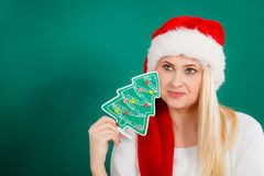 Woman in Santa hat holding little Christmas tree. Royalty Free Stock Photography