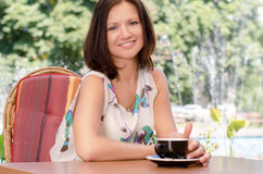 Enjoying a cup of coffee outdoors. Attractive smiling woman enjoying a cup of coffee outdoors at a table in her summer garden Stock Image