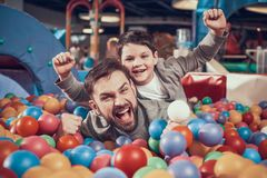 Enjoying dad and son in pool with balls. Family rest, leisure. Spending holiday together with family. Entertainment center, mall, amusement park royalty free stock images