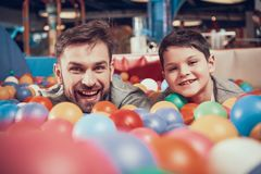 Enjoying dad and son in pool with balls. Family rest, leisure. Spending holiday together with family. Entertainment center, mall, amusement park royalty free stock photo