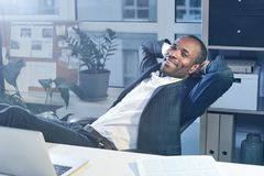 Optimistic stylish manager is expressing gladness. Enjoying day. Joyful elegant young african businessman in suit is relaxing on chair while stretching arms royalty free stock photos