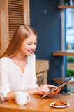 Enjoying a digital age. Side view of beautiful young woman using digital tablet and smiling while enjoying coffee in cafe stock photo