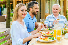 Enjoying dinner with family. Happy family enjoying meal together while women holding wine glass and smiling Royalty Free Stock Photography