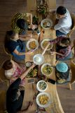 Enjoying dinner with friends. Top view of group of people having dinner together while sitting at the rustic wooden table Royalty Free Stock Images