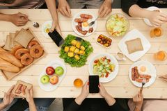 Enjoying dinner with friends. Top view of group of people having dinner together while sitting at wooden table stock images