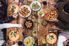 Enjoying dinner together. Top view of four people having dinner together while sitting at the rustic wooden table Royalty Free Stock Photos