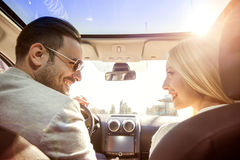 Enjoying the drive. A young women and a young men are laughing in the car, enjoying in the road trip. The men is driving Royalty Free Stock Image
