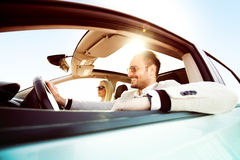 Enjoying the drive. A young women and a young men are laughing in the car, enjoying in the road trip. The men is driving Stock Photography