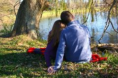 Enjoying each other's company and love. Young couple sitting under a tree Royalty Free Stock Images