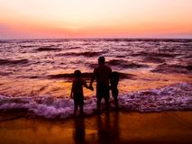Enjoying the evening sea breeze on bright orange sunset. A Loving father with his two children Royalty Free Stock Photography