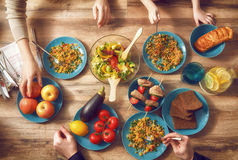 Enjoying  family dinner. Top view of family having dinner together sitting at the rustic wooden table. Enjoying  family dinner together Stock Photo