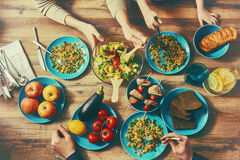Enjoying  family dinner. Top view of family having dinner together sitting at the rustic wooden table. Enjoying  family dinner together Royalty Free Stock Image