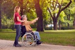 Enjoying in family time elderly man in wheelchair and daughter i. Enjoying in family time elderly men in wheelchair and smiling daughter in the park Stock Photo