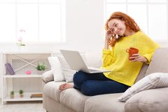 Enjoying free time at home. Smiling girl with laptop on sofa. Young happy woman in casual clothes videochatting via laptop and drinking coffee while sitting Royalty Free Stock Photo