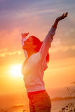 Enjoying freedom and life on sunset. Woman enjoying freedom and life on beautiful and magical sunset. Blissful girl raising arms feeling free, relaxed and happy Stock Photos