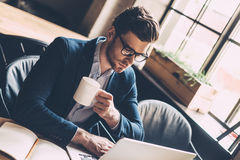Enjoying fresh coffee while working. Confident young man in smart casual wear working on laptop and holding coffee cup while sitting at his working place in Stock Photography